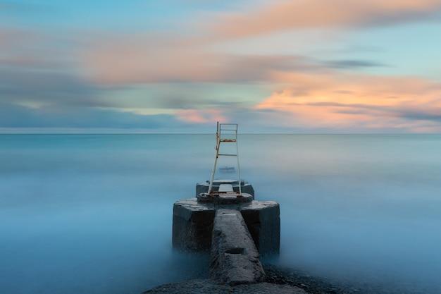 Lange blootstelling zeegezicht bij zonsopgang met wazig water kleurrijke wolken en betonnen pier in het midden van het frame met een badmeesterpost