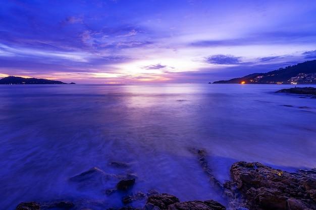 Lange blootstellingsbeeld van dramatisch hemelzeegezicht met rots in de achtergrond van het zonsonderganglandschap verbazingwekkende landschapsaardzee.