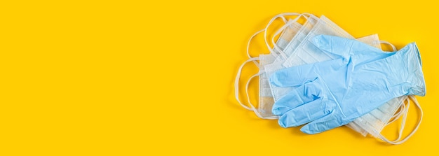Lange brede banner. paar medische latexhandschoenen en chirurgisch oor-lusmasker op gele achtergrond. hygiënebescherming coronavirus covid 19.