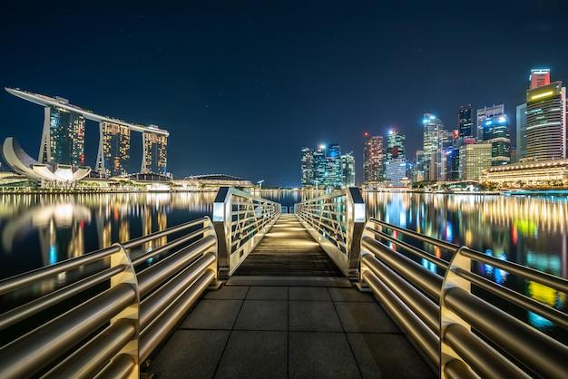 Lange brug tussen verlichte stad 's nachts