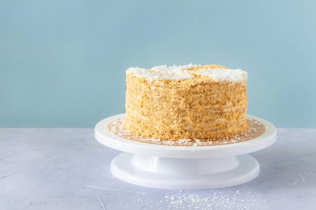 Lange cake versierd met kokosvlokken op wit dienblad.