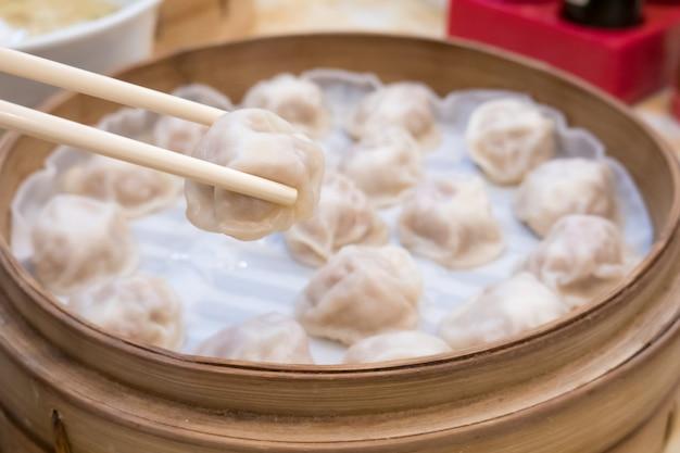 Lange de bamboedeknobels van xiao met eetstokjes in restaurant