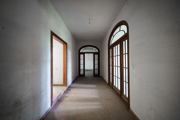 Lange gang van een oud verlaten herenhuis met deuren