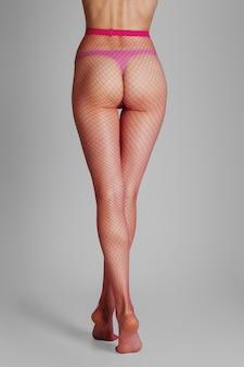 Lange gespierde vrouwelijke benen in sexy roze netkousen. achteraanzicht.