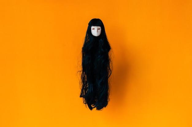 Lange haar vrouwelijke spookpop die op oranje achtergrond vliegt. minimaal halloween eng concept.