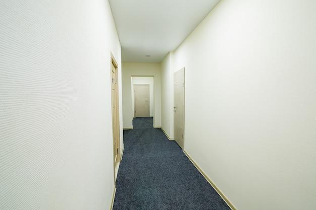 Lange heldere gang met deuren in een nieuw hotel, hostel