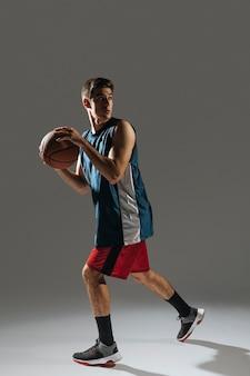 Lange jonge man training voor basketbalspel