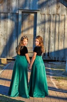 Lange jurk tweelingzusjes hand in hand
