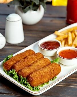 Lange kipnuggets geserveerd met friet, ketchup en zoete chilisaus