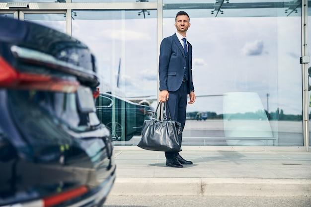 Lange knappe brunette man die een tas vasthoudt terwijl hij voor een terminal staat te wachten op transport