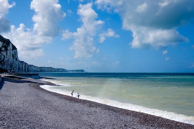 Lange kustlijn en witte kliffen met twee kinderen die met de golven spelen
