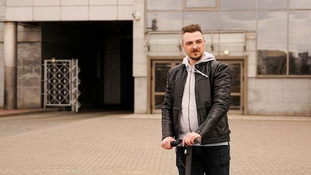 Lange man op een elektrische scooter tegen de achtergrond van grijze stadsgebouwen