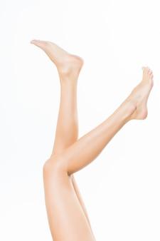 Lange mooie vrouwenbenen die op witte muur worden geïsoleerd
