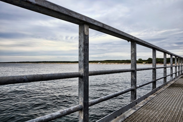 Lange pier in de zee met golven op het water tijdens zonsondergang of zonsopgang, zeegezicht aan de oostzee