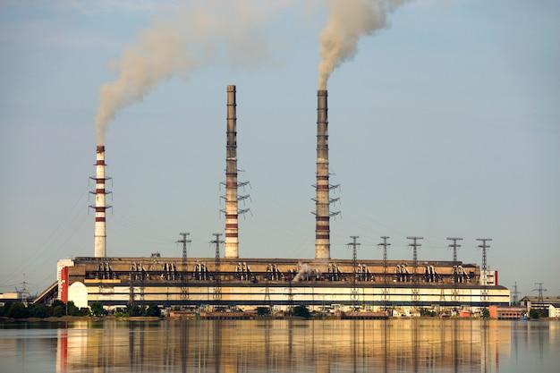 Lange pijpen van de thermische krachtcentrale met dikke rook die in lke waterspiegel worden weerspiegeld. vervuiling van het milieu.