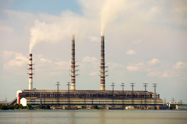 Lange pijpen van de thermische krachtcentrale met dikke rook die in lke waterspiegel worden weerspiegeld.