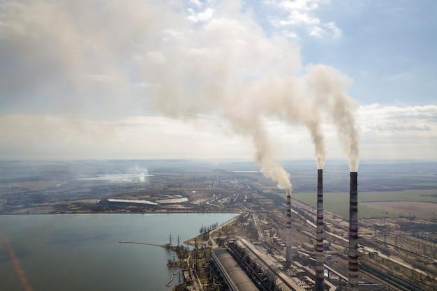 Lange pijpen van elektrische centrale, witte rook op landelijk landschap, meerwater en blauwe hemel.