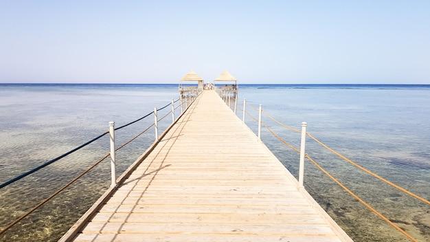 Lange ponton op de rode zee in egypte. ponton voor afdaling in het water. houten brug op het grondgebied van het amway hotel in sharm el sheikh met metalen hekken en een touw over de zee met golven.