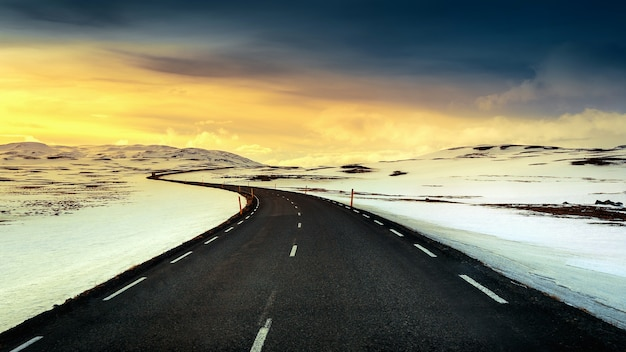 Lange rechte weg bij zonsondergang in de winter.