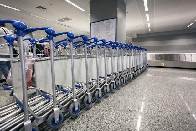 Lange rij bagagekarren bij luchthaventerminal