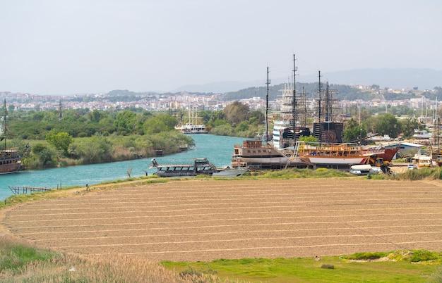 Lange schepen en toeristenboten afgemeerd langs een kronkelende rivier