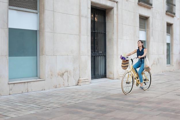 Lange schot vrouw op de fiets
