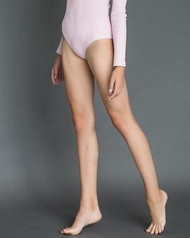 Lange slanke benen van een jong meisje op een grijze achtergrond zonder schoenen. foto op blote voeten tot aan de taille. zacht roze romper. daglicht. verzorging van de huid van het lichaam.
