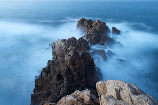Lange sluitertijd van de rotsen op het strand
