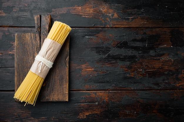 Lange spaghetti. ruwe spaghetti set, op houten snijplank, op oude donkere houten tafel