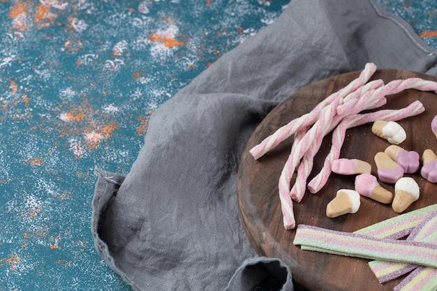 Lange, spiraalvormige en ijsvorm jellybeans op een houten bord. Gratis Foto
