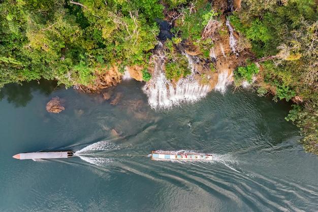 Lange staartboot die houten vlot dichtbij waterval slepen die in rivierkwai stroomt