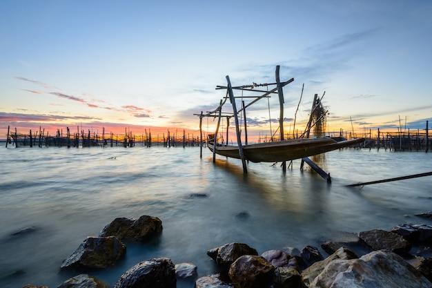 Lange staartboot in overzees met rotsen op zonsonderganghemel