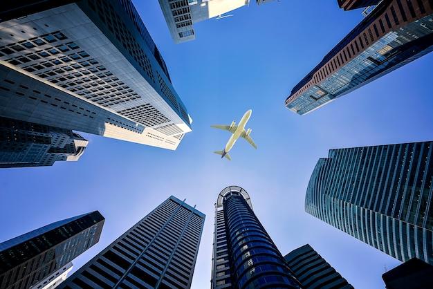 Lange stadsgebouwen en een vliegtuig dat boven vliegt