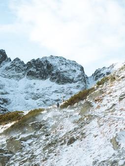 Lange verticale opname van een winterlandschap met een man die wandelt in het tatra-gebergte in polen