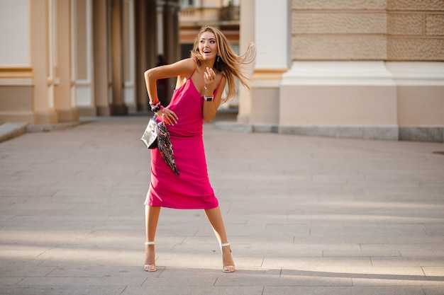 Lange volledige hoogte elegante glimlachende gelukkig aantrekkelijke vrouw in roze sexy zomerjurk lang haar wandelen in straat met handtas