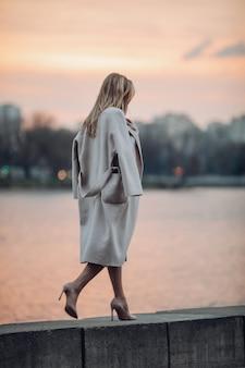 Lange vrouw in schoenen en jas wandelen in de buurt van de rivier