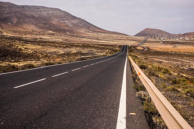 Lange weg rechte weg in het midden van een niemandsland landschap