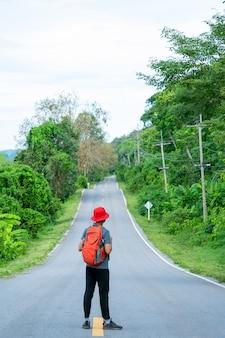 Lange weg te gaan, toerist die zich op de weg bevindt. reisconcept. uitdaging van reis.