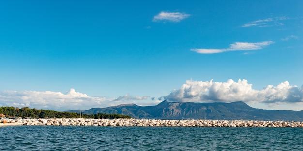 Lange witte rotsachtige pier in de ionische zee met helder water