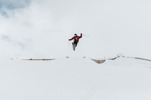 Langgeschoten skiër met uitrusting springen