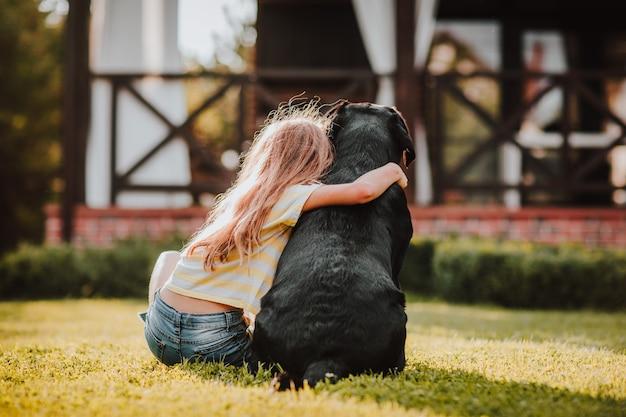 Langharig jong meisje in een gestript zomershirt dat bij haar rug op groen gras zit met een zwarte labrador retriever. uitzicht vanaf de achterkant.