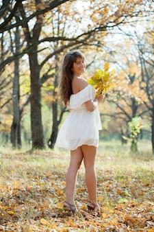 Langharig meisje met eik posy in de herfst