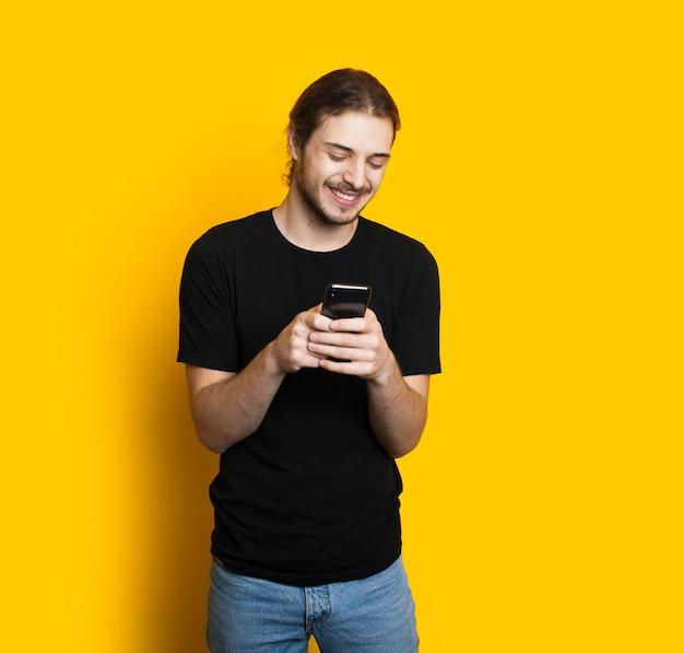 Langharige blanke jongen met baard sms't met iemand die een telefoon gebruikt terwijl hij zich voordeed op een gele achtergrond