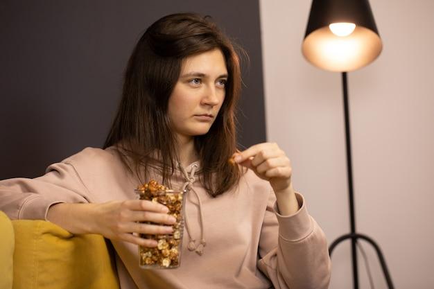 Langharige brunette meisje zittend knieën gebogen houden plastic beker popcorn