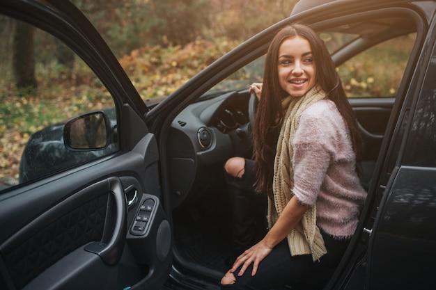 Langharige brunette op de auto. een vrouwelijk model draagt een trui en een sjaal. herfst . herfst bos reis met de auto