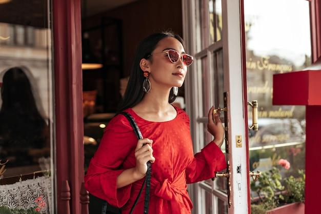 Langharige brunette vrouw in rode zonnebril en trendy lichte jurk kijkt weg en opent cafédeur