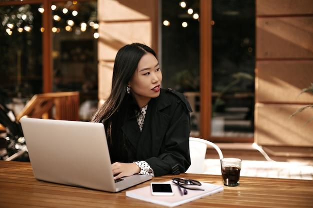 Langharige brunette vrouw in zwarte stijlvolle jas zit aan houten bureau en werkt met laptop