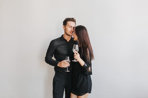 Langharige brunette vrouw omarmen haar vriendje tijdens het dansen op verjaardagsfeestje