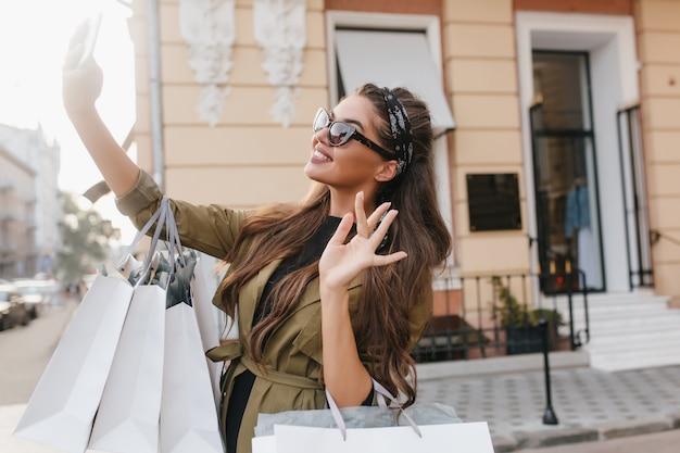 Langharige brunette vrouw selfie maken tijdens wandeling door de stad en lachen