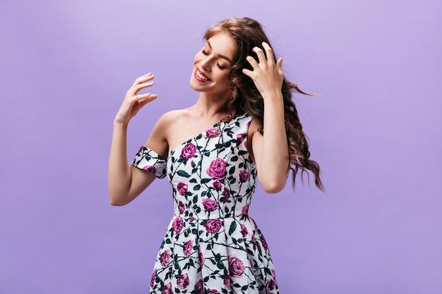 Langharige dame in een mooie jurk vormt op paarse achtergrond. krullend blije vrouw in bloemenkleren schattig lachend op geïsoleerde achtergrond.